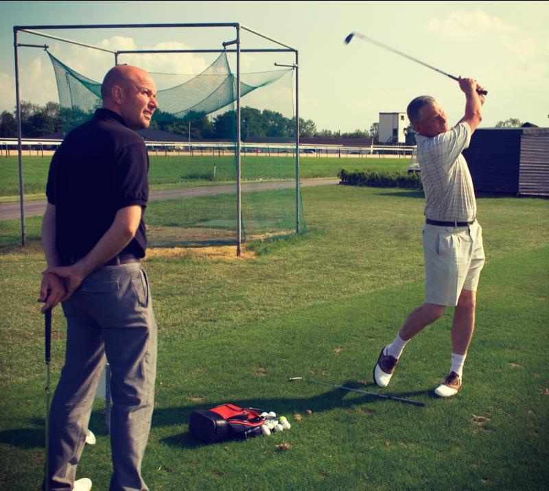 Two men playing golf, with one of them mid-swing.