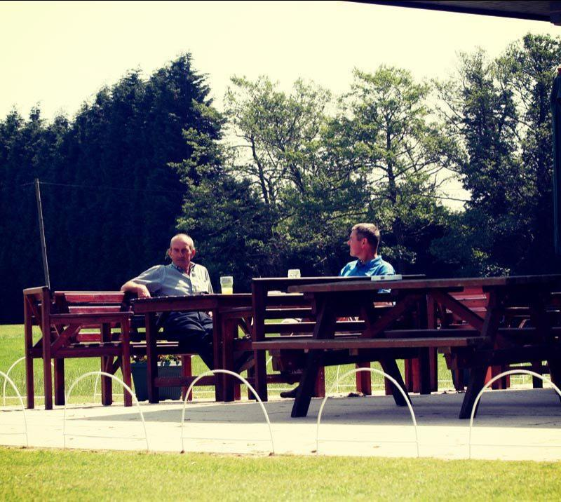 Two men sitting on benches at the Southwell Golf Club.