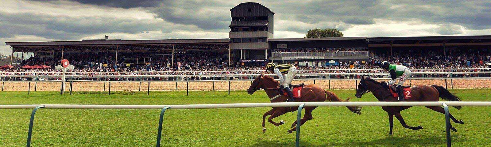 Jockeys racing past the finishing post at Southwell Racecourse.