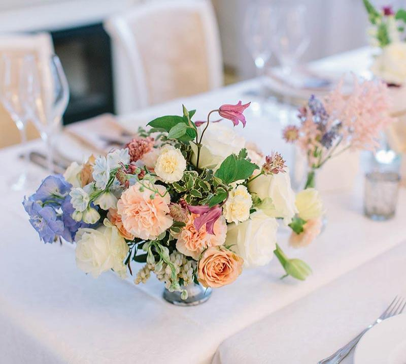 A bouquet of flowers sits on a wedding breakfast table.