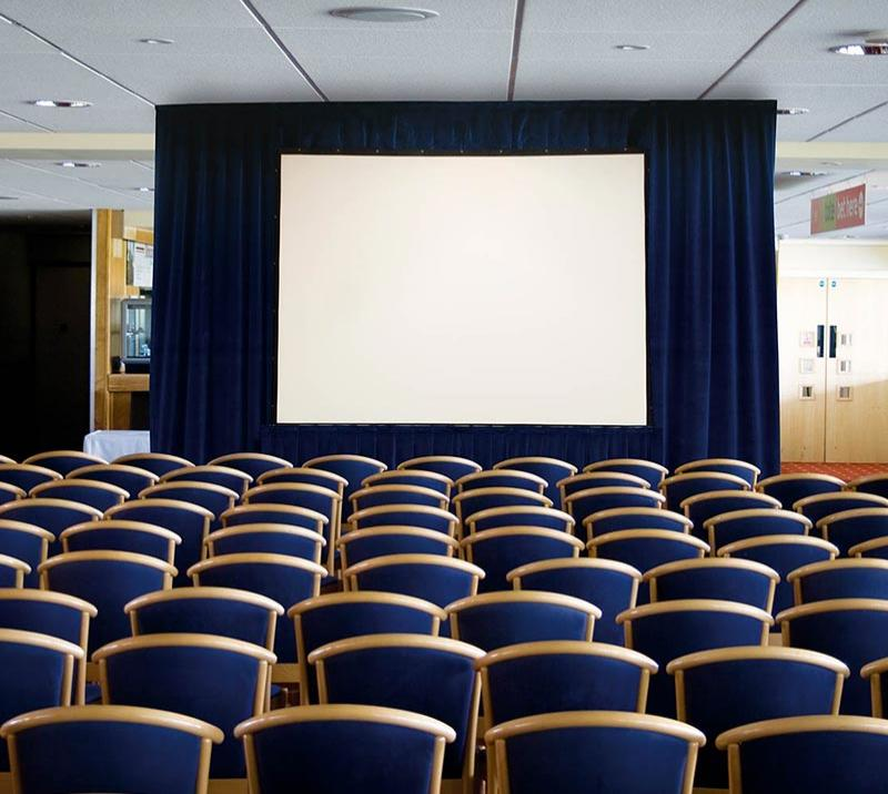 Rows of chairs face a stage with a projector screen.