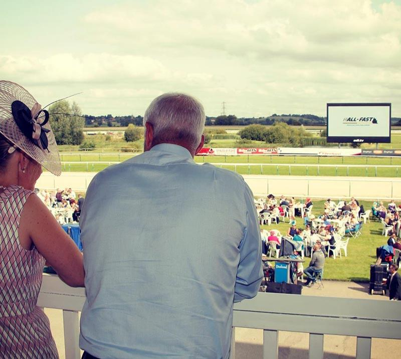 Racegoers standing on the balcony overlooking the track.