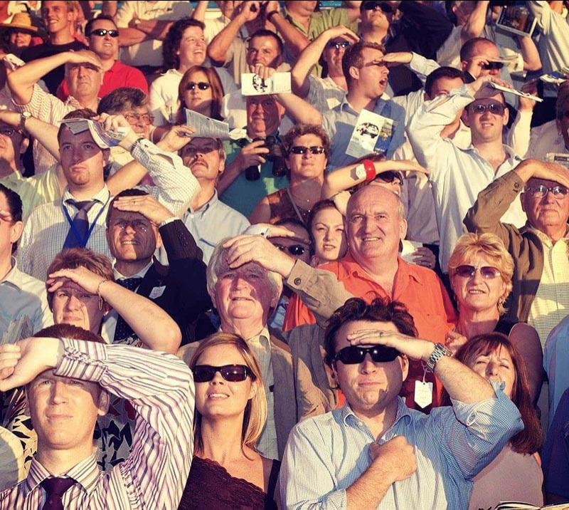 Crowds at Southwell Racecourse shielding their eyes from the sun